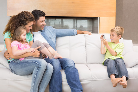 homey: Little boy taking photo of family on the sofa at home in living room