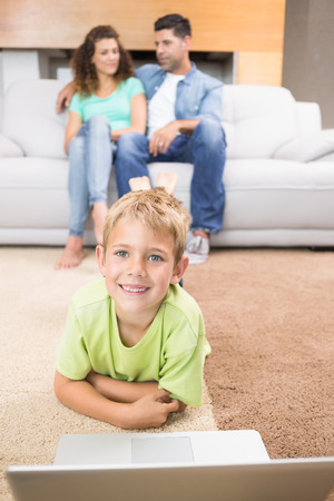 Happy little boy using laptop on the rug with parents sitting sofa at home in living room photo