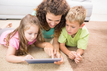 Happy siblings lying on the rug using tablet with their mother at home in living room photo