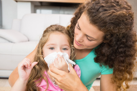 curly hair child: Mother helping her daughter blow her nose at home in living room