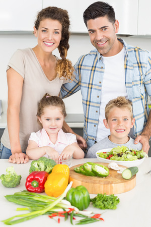 Happy family preparing vegetables together at home in kitchen photo