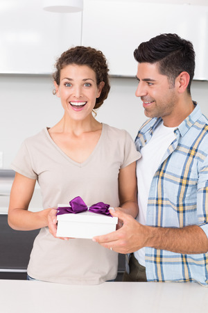 Surprised woman holding a gift from her partner at home in kitchen photo