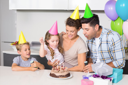 Happy young family celebrating a birthday together at home in kitchen photo
