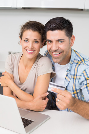 Attractive couple using laptop together to shop online at home in kitchen photo