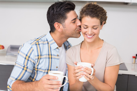 hot drink: Happy woman drinking coffee getting a kiss from partner at home in kitchen