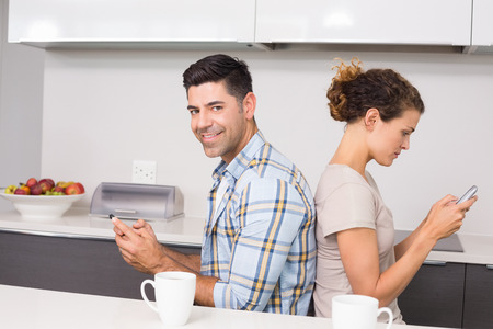 back kitchen: Couple sitting back to back texting with man smiling at camera at home in kitchen