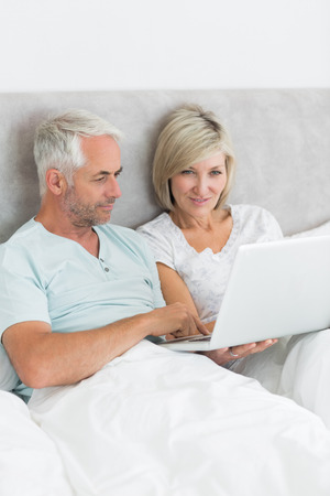 Portrait of a happy mature couple using laptop in bed at home photo