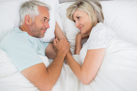 bed sheet: Loving mature man and woman lying in bed at the home