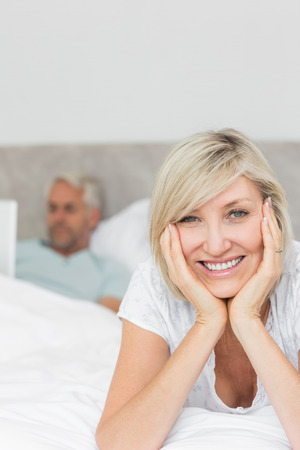 Portrait of a happy mature woman with man using laptop in bed at home photo