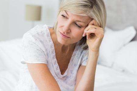 Primer plano de una mujer madura tensa sentado en la cama en su casa Foto de archivo