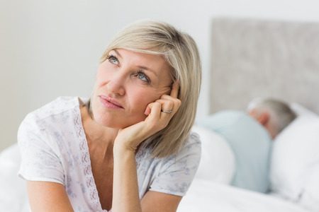 Closeup of a tensed mature woman sitting in bed with man in background at home photo