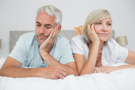 Closeup of displeased mature man and woman lying in bed at home photo