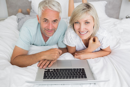 Portrait of a relaxed mature couple using laptop in bed at home photo