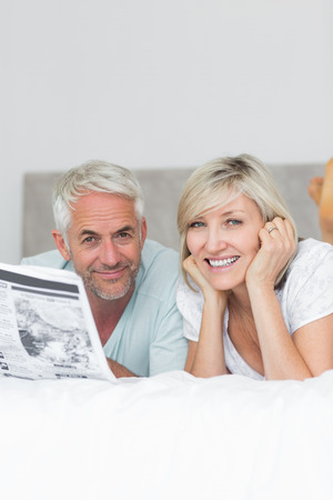 Portrait of a smiling mature couple reading newspaper in bed at home photo