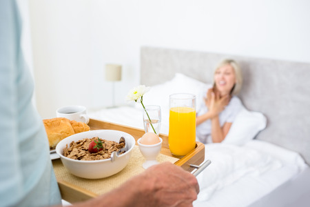 Blurred mature woman sitting in bed with breakfast in foreground at home photo