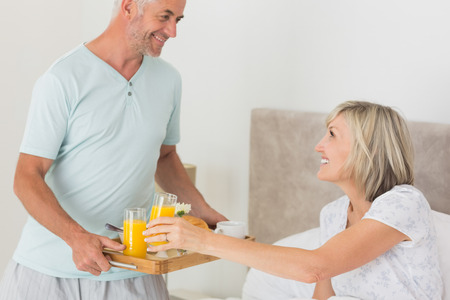 Mature man serving woman breakfast in bed at home photo