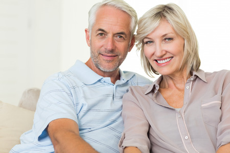 adult couple: Portrait of a smiling mature couple sitting on sofa at home Stock Photo