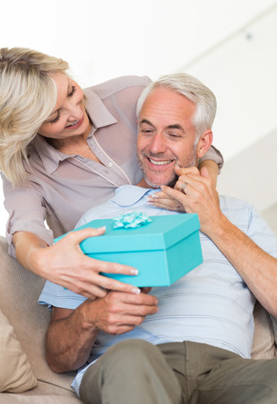 gifting: Portrait of a smiling woman surprising mature man with a gift on sofa at home Stock Photo