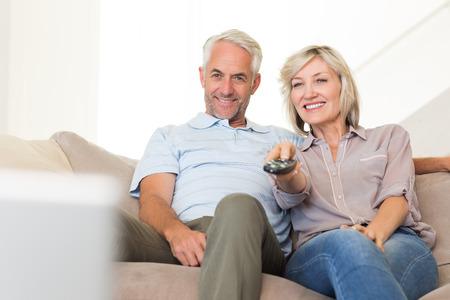 pareja viendo tv: Feliz pareja madura viendo la televisi�n en el sof� en casa Foto de archivo