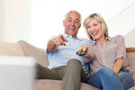 Cheerful mature couple watching tv on sofa at home photo