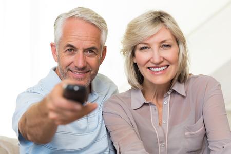 pareja viendo tv: Retrato de la feliz pareja madura viendo la televisi�n en el sof� en casa