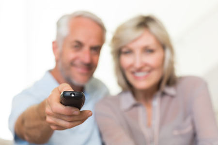 Blurred happy mature couple watching tv on sofa at home photo