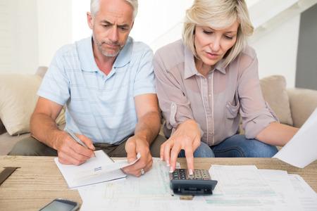 pareja en casa: Hombre maduro concentrado y la mujer con las cuentas y calculadora sentado en el sof� en casa Foto de archivo