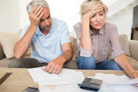 tensed: Tensed mature man and woman with bills and calculator sitting on sofa at home