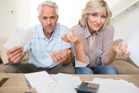 Tensed mature man and woman with bills and calculator sitting on sofa at home photo