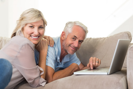Portrait of a happy mature couple using laptop on sofa at home photo