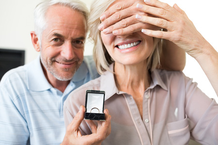 Closeup portrait of a smiling man surprising woman with a wedding ring photo