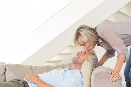 Side view of a woman kissing a relaxed mature mans forehead in the living room at home photo