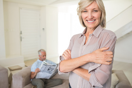 Portrait of a smiling woman with man reading newspaper in background at home photo