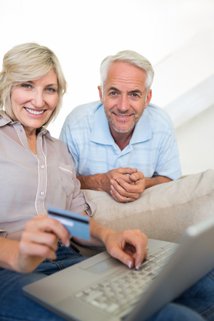 Casual mature couple doing online shopping through computer and credit card at home photo