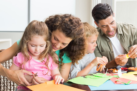Cheerful family doing arts and crafts together at the table at home in kitchen photo