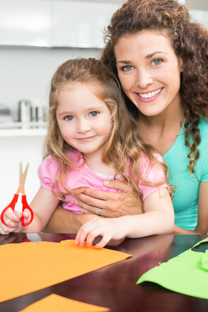 Happy little girl making paper shapes with mother at the table at home in kitchen photo