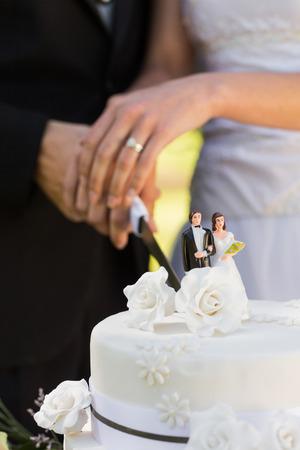 中央部新婚結婚式ケーキカットの極端なクローズ アップ