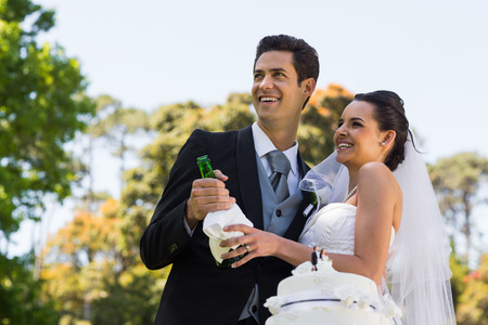 Happy young newlywed couple with champagne bottle at the park photo