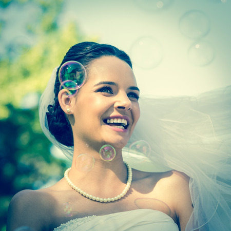 beautiful bride: Close-up of a young beautiful bride looking at soap bubbles in the park