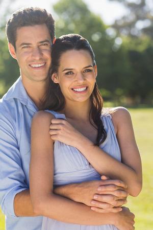 mujer de espaldas: Retrato de un hombre sonriente abrazando a mujer por detr�s en el parque