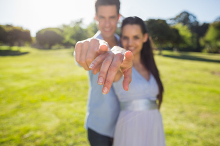 Portrait of a happy young couple pointing finger to the camera at the park photo