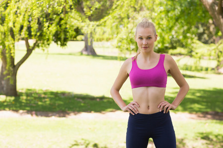 body concern: Portrait of a healthy and beautiful young woman in sports bra standing in the park