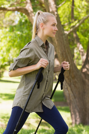 Side view of a beautiful young woman Nordic walking in the park photo