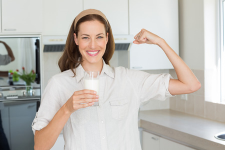 tricep: Portrait of a happy young woman flexing muscles while drinking water in the kitchen at home