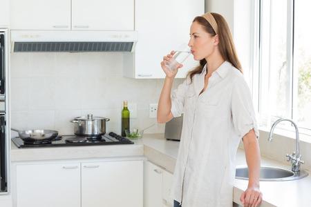 tomando agua: Vista lateral de una joven mujer de agua potable en la cocina en el hogar Foto de archivo