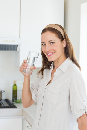 standing water: Portrait of a young woman drinking water in the kitchen at home