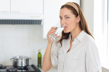 drinking water: Portrait of a young woman drinking water in the kitchen at home