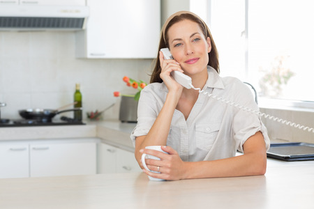 Portrait of a smiling young woman with coffee cup using landline phone in the kitchen at home