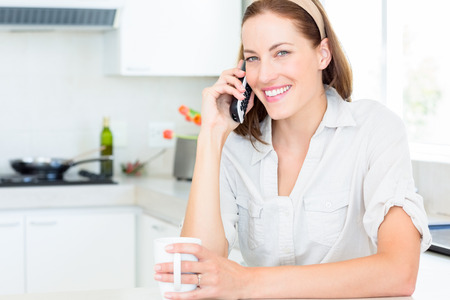 Portrait of a smiling young woman with coffee cup using mobile phone in the kitchen at home photo