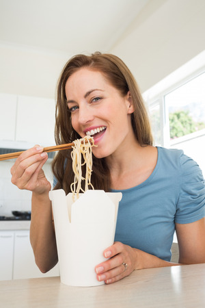 eating noodles: Portrait of a smiling young woman eating noodles in the kitchen at home